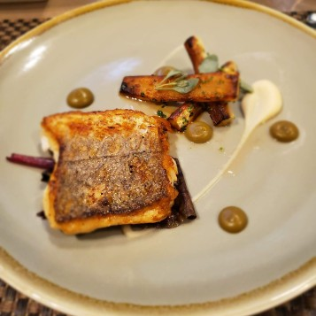Hake cooked with capers, golden raisins, salsify, parsley root, rainbow chard